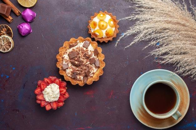 Draufsicht auf köstliche kuchen zusammen mit zimttee und süßigkeiten auf der dunklen oberfläche