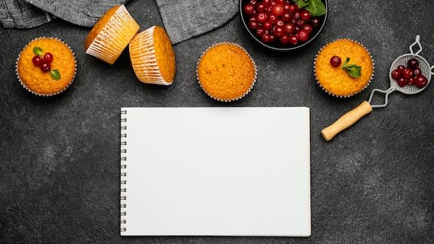 Draufsicht auf köstliche muffins mit beeren und notizbüchern