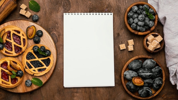 Draufsicht auf köstliche obstkuchen mit pflaumen und notizbuch