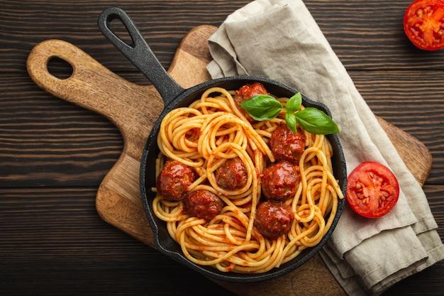 Draufsicht auf köstliche pasta mit fleischbällchen, tomatensauce und frischem basilikum in rustikaler vintage-pfanne aus gusseisen, serviert auf schneidebrett, holzhintergrund. leckere hausgemachte frikadellen spaghetti