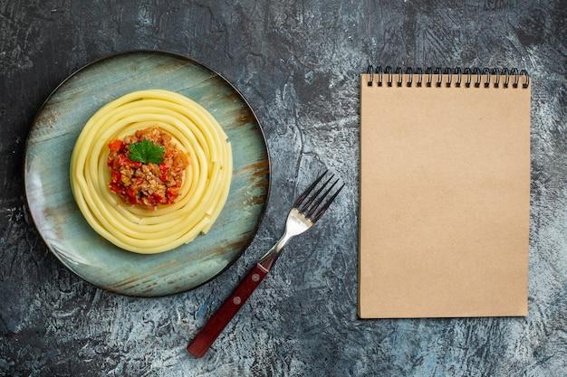 Draufsicht auf köstliche pastagerichte auf einem blauen teller, serviert mit tomaten und fleisch zum abendessen und gabel und geschlossenem notizbuch