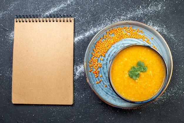 Draufsicht auf köstliche rote linsensuppe in einer schüssel, serviert mit grün auf blauem tablett und spiralnotizbuch auf schwarzem weißem hintergrund mit freiem platz