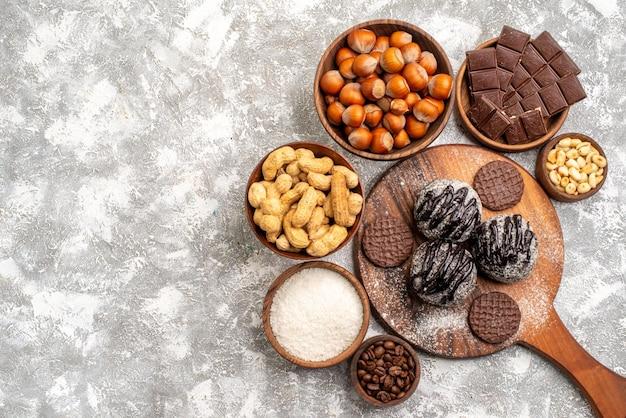 Draufsicht auf köstliche schokoladenkuchen mit keksen, nüssen und erdnüssen auf weißer oberfläche