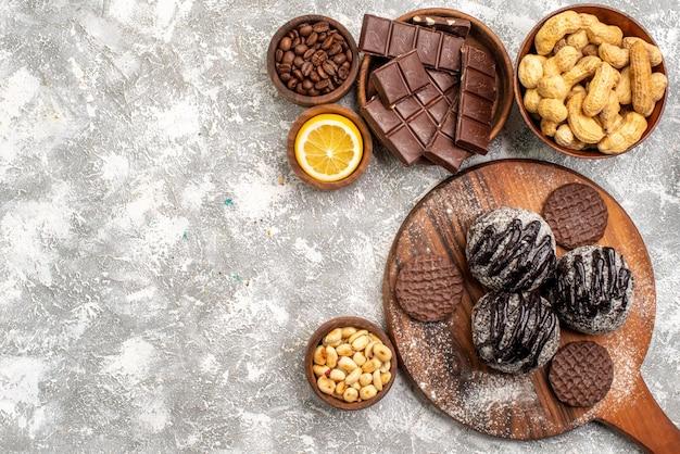 Draufsicht auf köstliche schokoladenkuchen mit keksen und erdnüssen auf der weißen oberfläche
