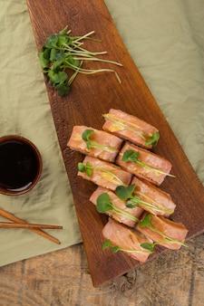 Draufsicht auf köstliche sushi-rollen mit zutaten auf holztisch
