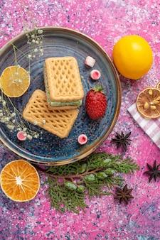 Draufsicht auf köstliche waffeln mit erdbeere und zitrone auf dem hellrosa schreibtisch