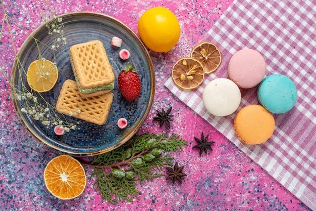 Draufsicht auf köstliche waffeln mit französischen macarons auf dem hellrosa schreibtisch