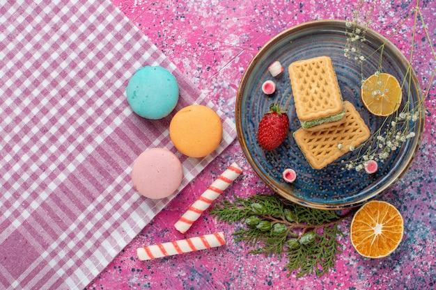 Draufsicht auf köstliche waffeln mit französischen macarons auf der hellrosa oberfläche