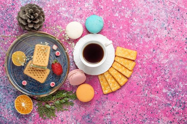 Draufsicht auf köstliche waffeln mit französischen macarons-crackern und tee auf rosa oberfläche