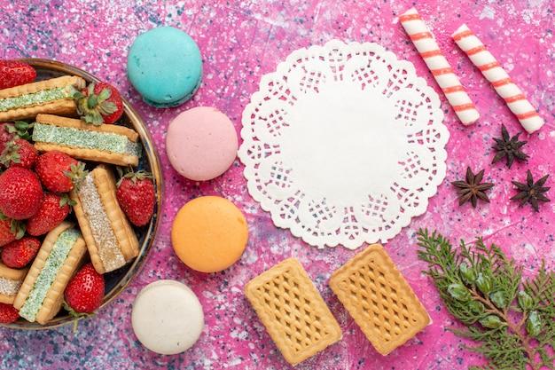 Draufsicht auf köstliche waffeln mit französischen macarons und marshmallows auf der rosa oberfläche
