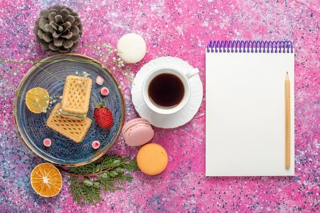Draufsicht auf köstliche waffeln mit französischen macarons und tee auf der rosa oberfläche