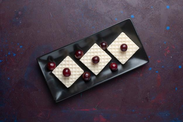 Draufsicht auf köstliche waffeln mit kirschen innerhalb platte auf der dunklen oberfläche