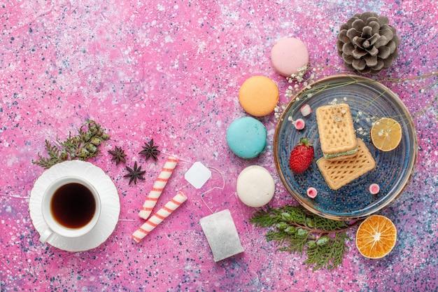 Draufsicht auf köstliche waffeln mit leckeren französischen macarons und tee auf dem rosa schreibtisch