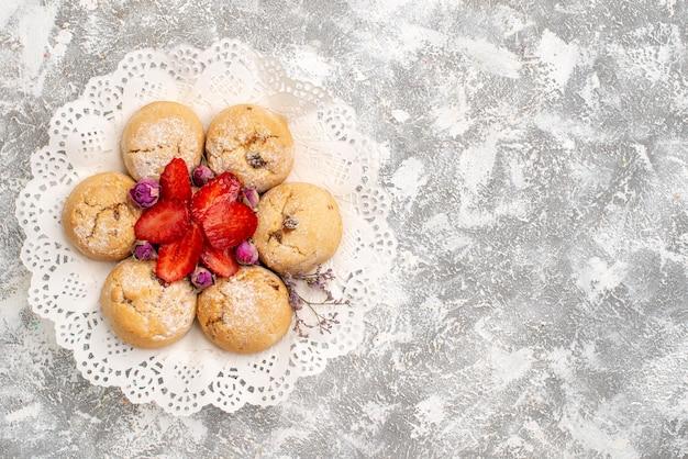 Draufsicht auf köstliche zuckerkekse mit erdbeeren auf weißer oberfläche