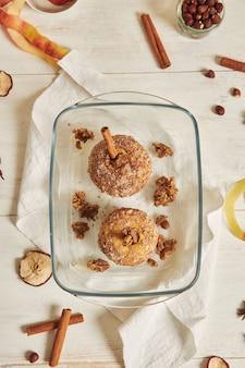Draufsicht auf köstlichen bratapfel mit nüssen und zimt auf einem weißen tisch