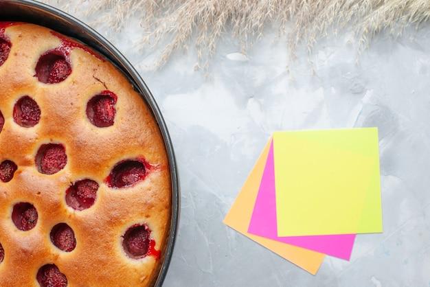 Draufsicht auf köstlichen erdbeerkuchen, der mit frischen roten erdbeeren innen mit pfanne und notizblock auf hellweißem schreibtisch gebacken wird, kuchenkeksfrucht süßer auflauf