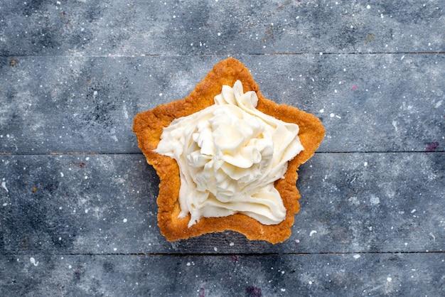 Draufsicht auf köstlichen gebackenen kuchenstern geformt mit weißer leckerer sahne innen auf hellem schreibtisch, kuchen backen zucker süßer sahne-tee