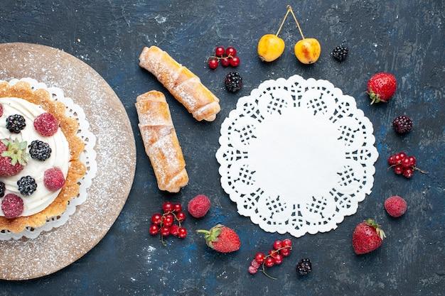 Draufsicht auf köstlichen kleinen kuchen mit zuckerpulvercreme und beeren zusammen mit armreifen auf dunkelheit