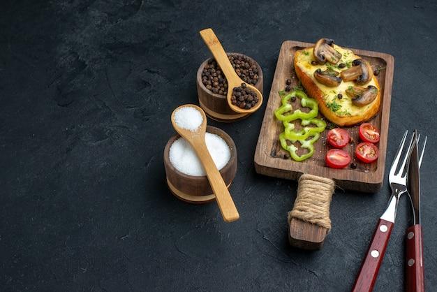 Draufsicht auf köstlichen snack mit frischem pilzgemüse und gewürzbesteck auf der linken seite auf schwarzem hintergrund