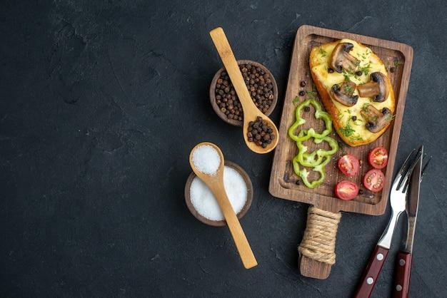 Draufsicht auf köstlichen snack mit frischem pilzgemüse und gewürzbesteck auf schwarzem hintergrund