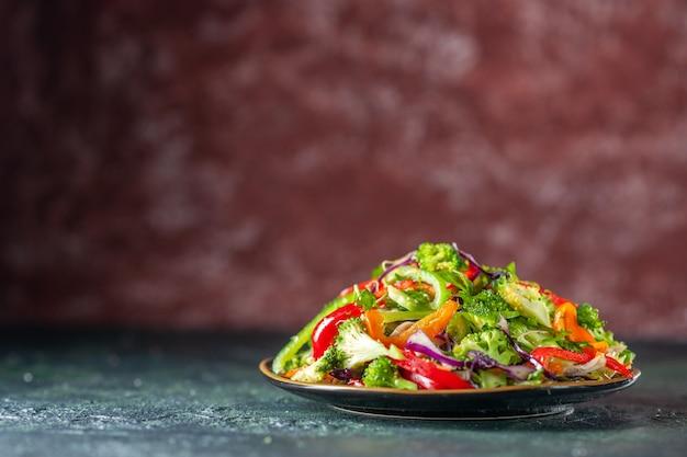 Draufsicht auf köstlichen veganen salat mit frischen zutaten in einem teller auf der linken seite auf blauem und kastanienbraunem, unscharfem hintergrund
