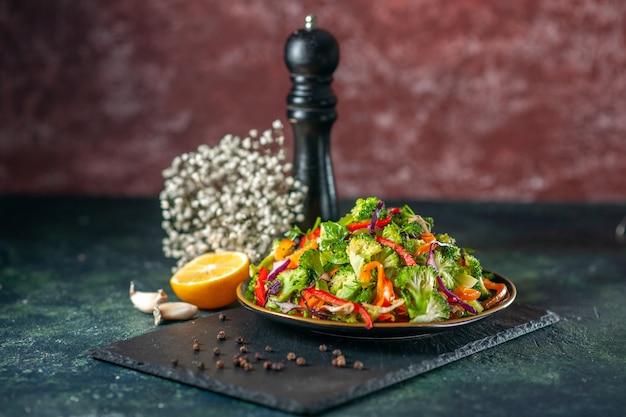 Draufsicht auf köstlichen veganen salat mit frischen zutaten in einem teller und pfeffer auf schwarzem schneidebrett
