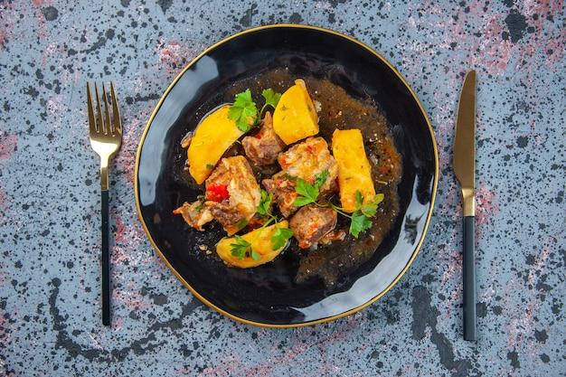 Draufsicht auf köstliches abendessen mit fleischkartoffeln, die mit grün in einem schwarzen teller und besteck auf mischfarbenhintergrund gesetzt werden