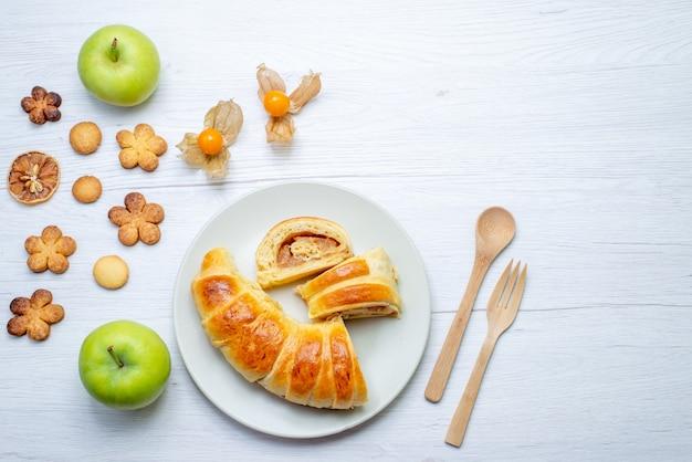 Draufsicht auf köstliches geschnittenes gebäck innerhalb des tellers mit füllung zusammen mit äpfeln und keksen auf weißem süßem zucker des gebäckplätzchenkekses