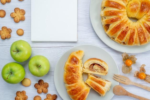 Draufsicht auf köstliches geschnittenes gebäck innerhalb des tellers mit füllung zusammen mit grünem apfelnotizblock und keksen auf weißem schreibtisch, gebäckkekskeks süß