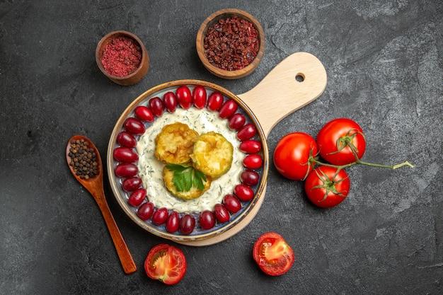 Draufsicht auf köstliches kürbismehl mit frischen roten hartriegel-tomaten und gewürzen auf grauer oberfläche