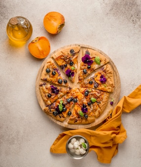 Draufsicht auf köstliches stück pizza mit blütenblättern und kakis
