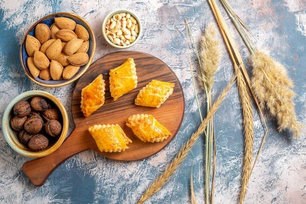 Draufsicht auf köstliches süßes gebäck mit nüssen auf blauer oberfläche