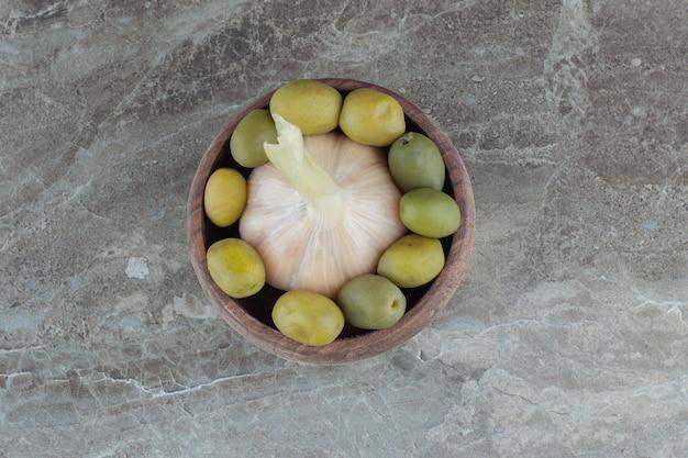 Draufsicht auf konservierte oliven mit knoblauch in holzschale.