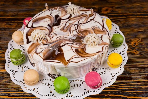 Draufsicht auf kuchen mit verschiedenen weißen schokoladenornamenten, in der nähe von macarons, auf holzschreibtisch