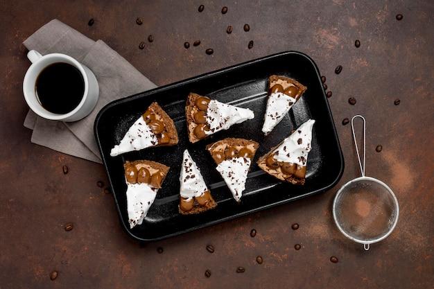 Draufsicht auf kuchenstücke auf tablett mit sieb und kaffee