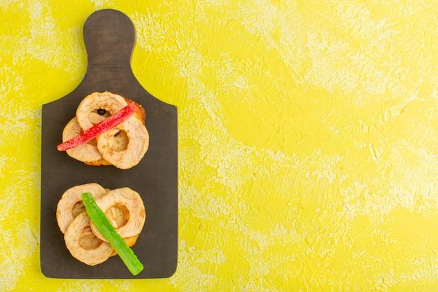 Draufsicht auf kuchenstücke mit getrockneten ananasringen und marmelade auf gelber oberfläche