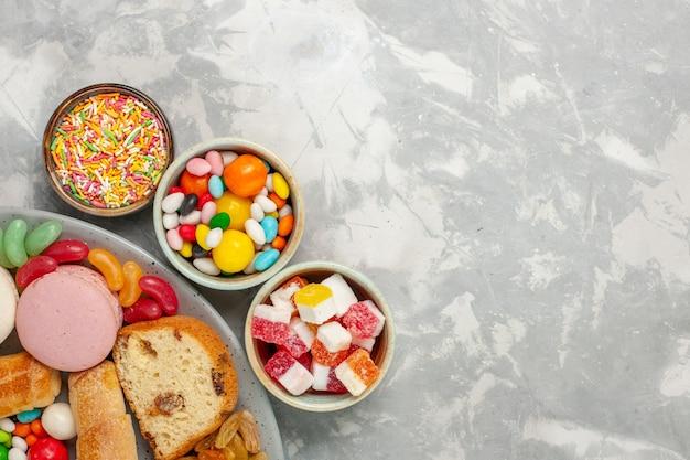 Draufsicht auf kuchenstücke mit macarons und bonbons