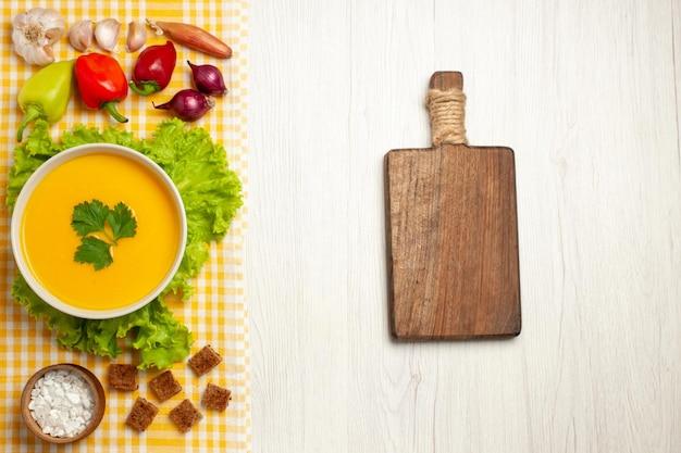 Draufsicht auf kürbissuppe mit gemüse auf hellweiß