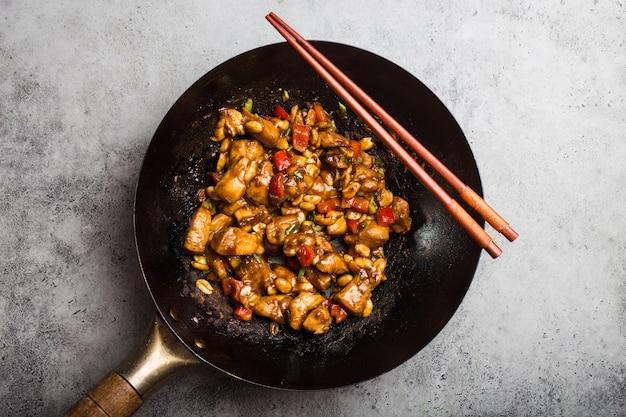 Draufsicht auf kung pao hühnchen, gebratenes chinesisches traditionelles gericht mit hühnchen, erdnüssen, gemüse, chilischoten in einer wok-pfanne. chinesisches abendessen, rustikaler betonhintergrund