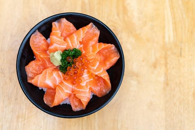 Draufsicht auf lachs don, frischen sashimi, rohen lachs, lachsrogen, wasabi auf holztisch. speicherplatz kopieren