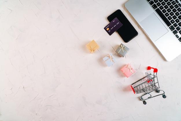 Draufsicht auf laptop, schwarze freitagsförderungsverkaufswörter auf leuchtkasten, geschenkboxen, wagen, kreditkarte und smartphone. flach liegen