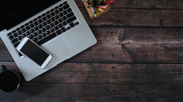 Draufsicht auf laptop, smartphone und notebook auf holztisch. kopieren sie platz für textnachrichten oder informationsinhalte.