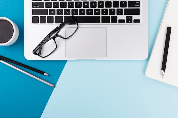 Draufsicht auf laptop und brille mit kopierraum