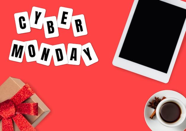 Draufsicht auf laptop und geschenk, geschenk mit cyber monday-schriftzug auf rotem hintergrund. copyspace für ihre werbung. schwarzer freitag, verkauf, finanzen, werbung, geld, finanzen, kaufkonzept.