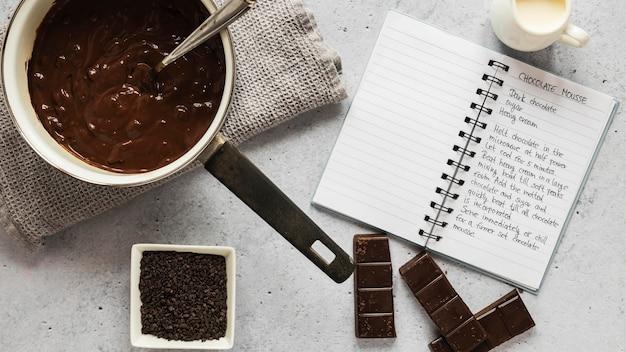 Draufsicht auf lebensmittelzutaten mit schokolade und notizbuch