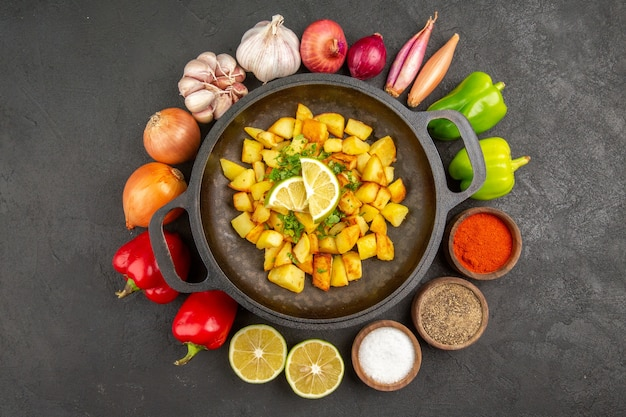 Draufsicht auf leckere bratkartoffeln in der pfanne mit verschiedenen gewürzen und gemüse auf dunkler oberfläche
