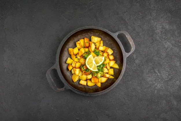 Draufsicht auf leckere bratkartoffeln in der pfanne mit zitronenscheiben auf der dunklen oberfläche Kostenlose Fotos