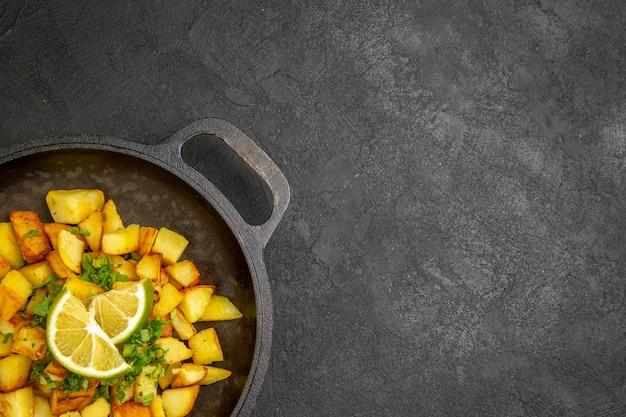 Draufsicht auf leckere bratkartoffeln in der pfanne mit zitronenscheiben auf der dunklen oberfläche