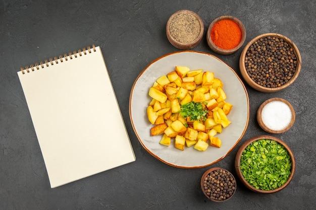 Draufsicht auf leckere bratkartoffeln in teller mit gewürzen auf der dunklen oberfläche Kostenlose Fotos