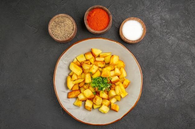 Draufsicht auf leckere bratkartoffeln in teller mit gewürzen auf der dunklen oberfläche
